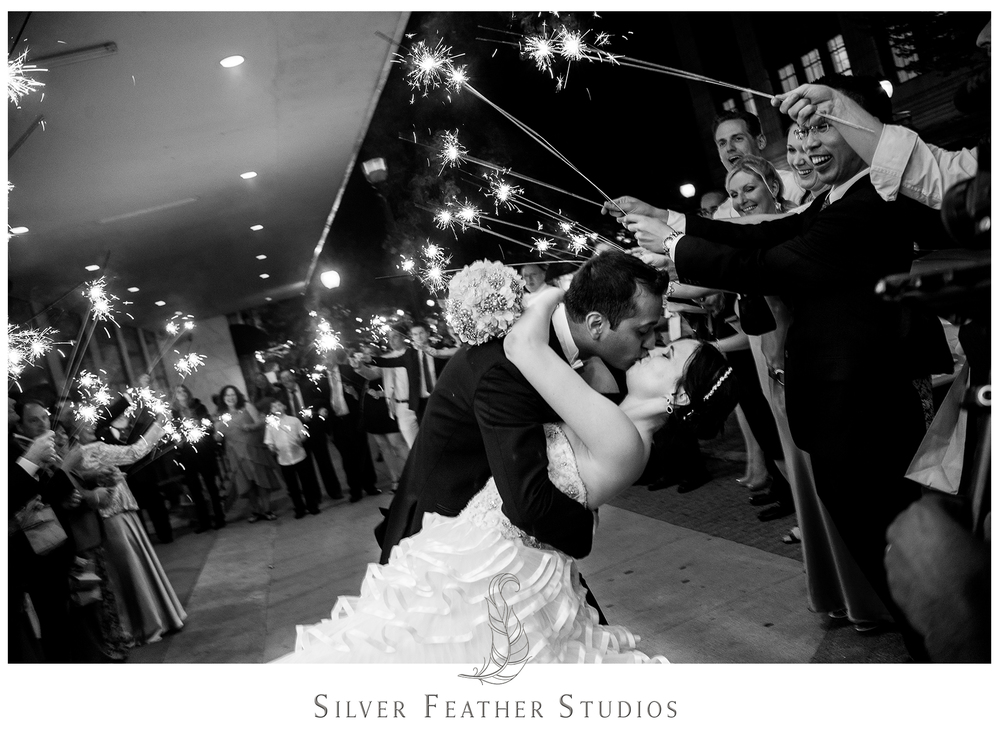 Sparkler exit and dipped kiss as Madison and Harsh exit their wedding at the Empire Room. © Silver Feather Studios, Greensboro wedding photography and videography.