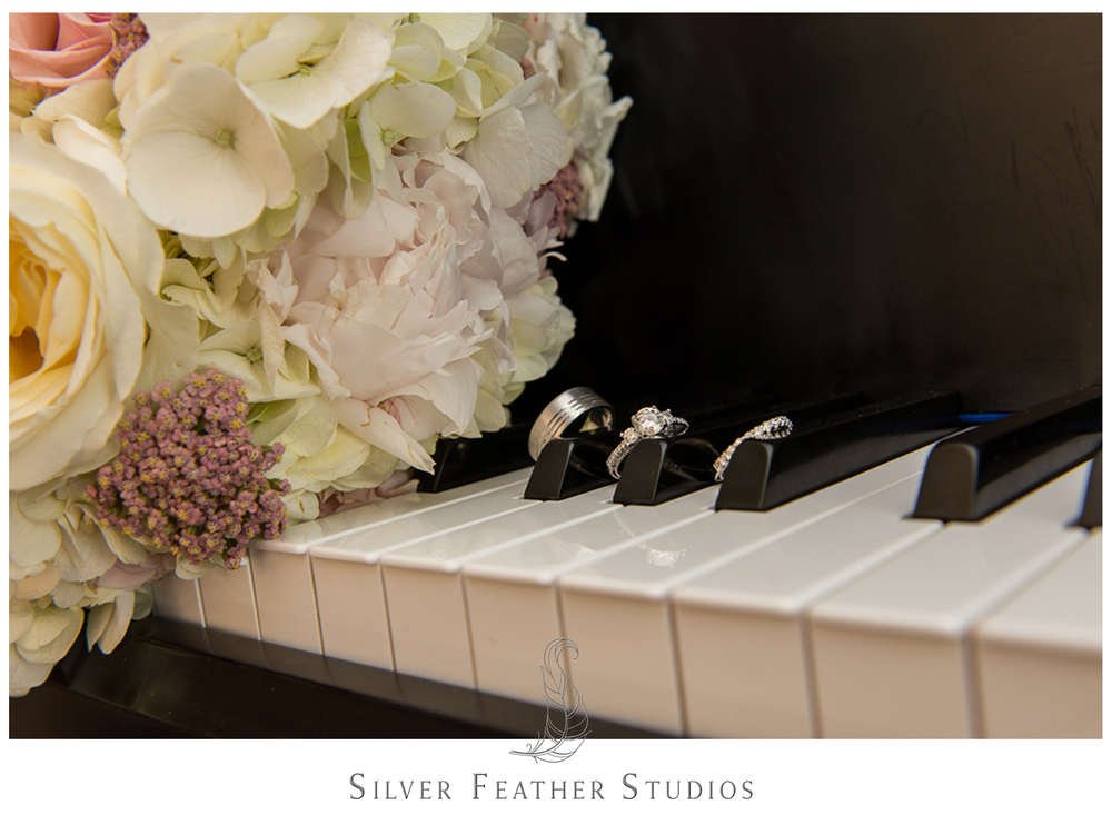 wedding details: bands, engagement ring, bouquet, on a piano. river landing wedding photographer.