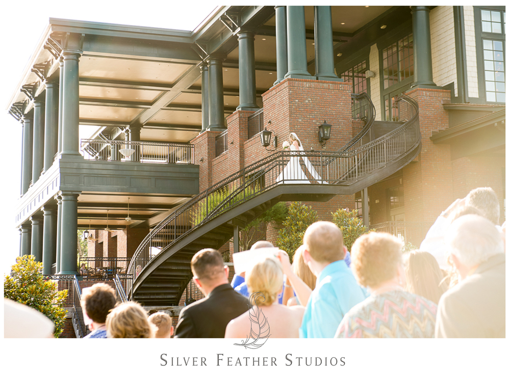 Burlington wedding photographer, Silver Feather Studios, photographs the bride walking down the talk spirla staircase at River Landing.