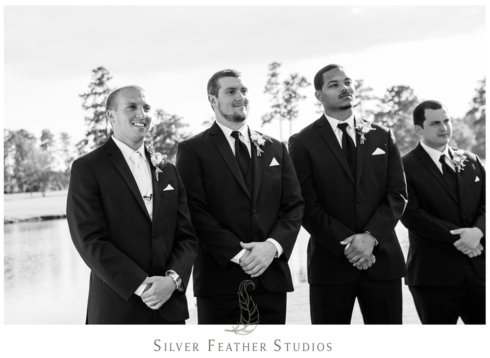 Black and white image of groom as he sees his bride for the first time at their River Landing wedding.