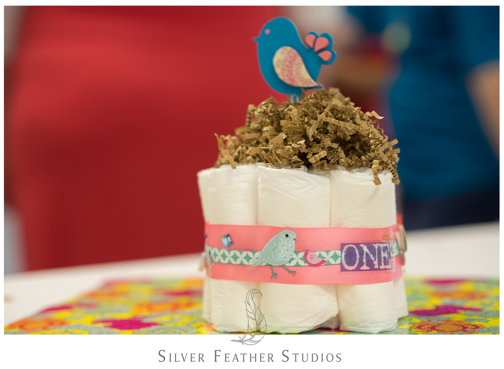 Diaper cake with bird nest of crinkled paper and blue bird. © Silver Feather Studios, Burlington wedding photographer.