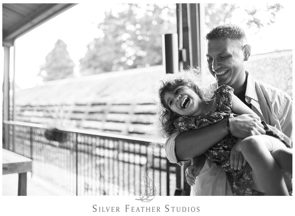 tickling their four year old at their belt line station engagement session in durham.