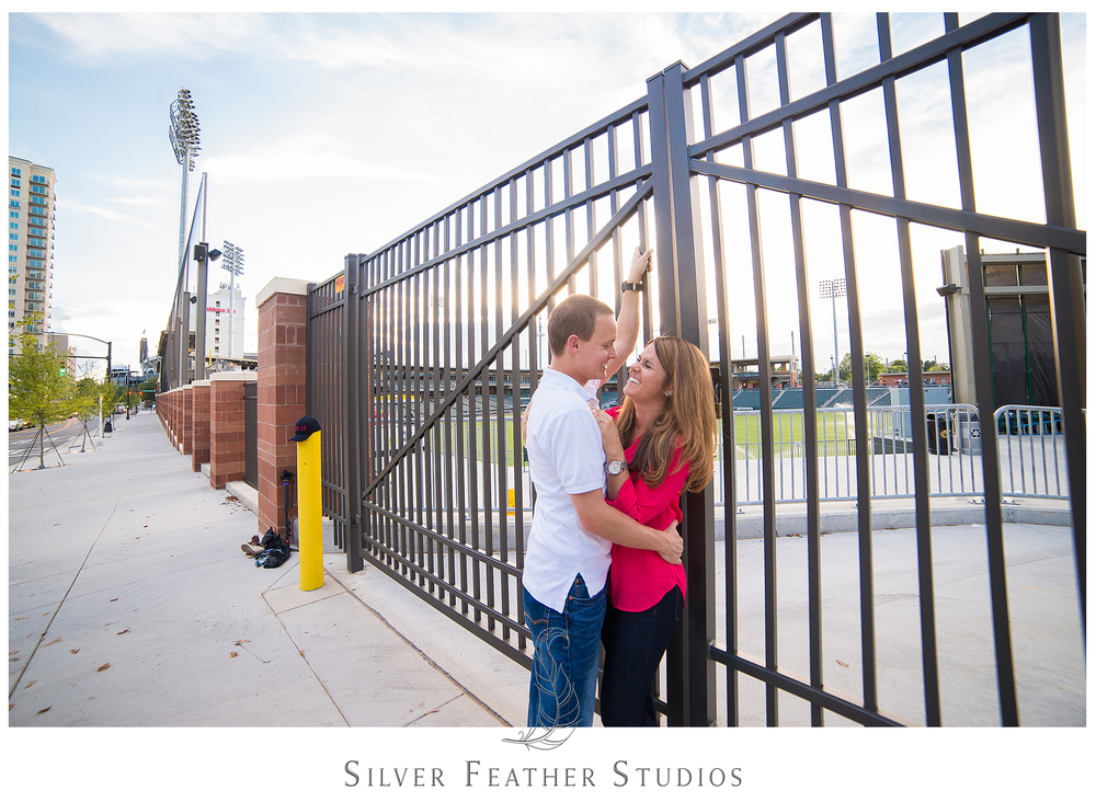 Couple pose in front of the Knights baseball stadium at their Uptown Charlotte engagement session.