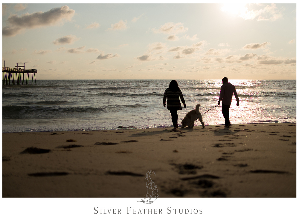 Burlington NC wedding photographer, Silver Feather Studios, silhouettes a couple and their dog on the Outer Banks.
