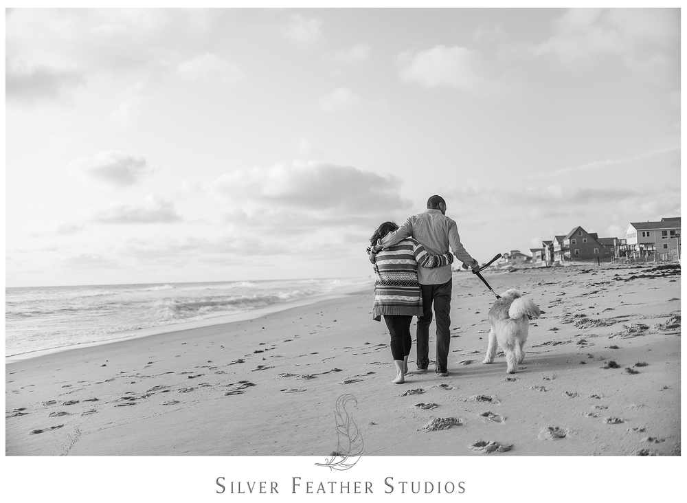 Lovely couple walk their labradoodle on the Outer Banks coast near Rodanthe, NC.