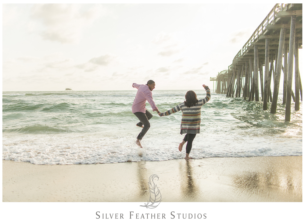 Kim and Wally jump around in the ocean near at their Outer Banks engagement session with Silver Feather Studios.