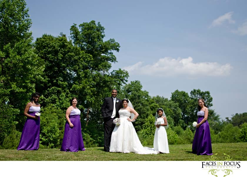 The bridesmaid pose with the couple in purple gowns.