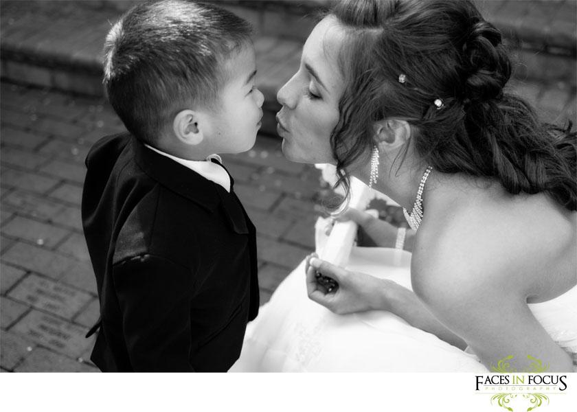 Bride kisses ring bearer in his tuxedo in Graham, NC