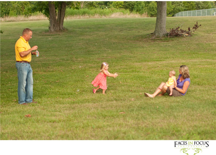 Traumuller family plays with bubbles in the field.