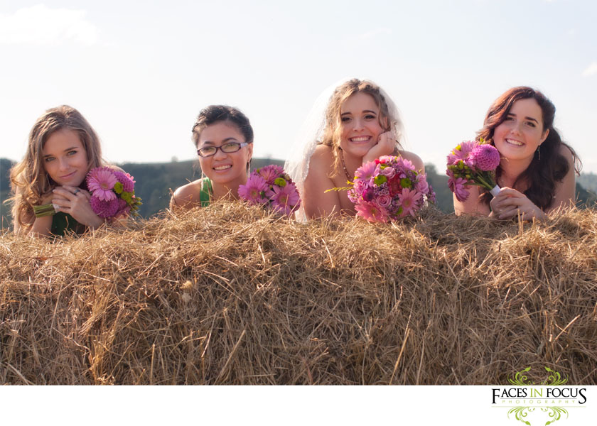 Bride and bridesmaids pose on hay bale.