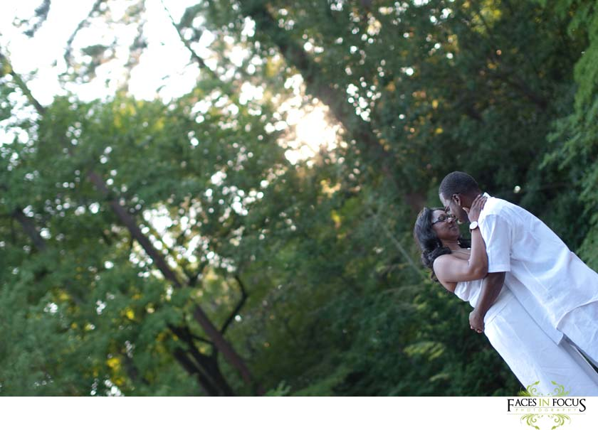 Durham, NC - The sun sets behind the couple over a red bridge at Duke Gardens.