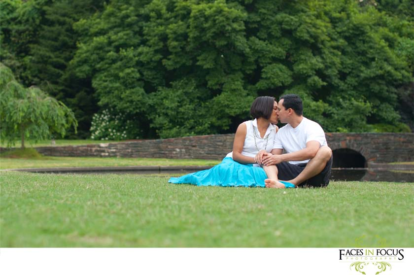 Family cuddles on lush green lawn at Duke Gardens.