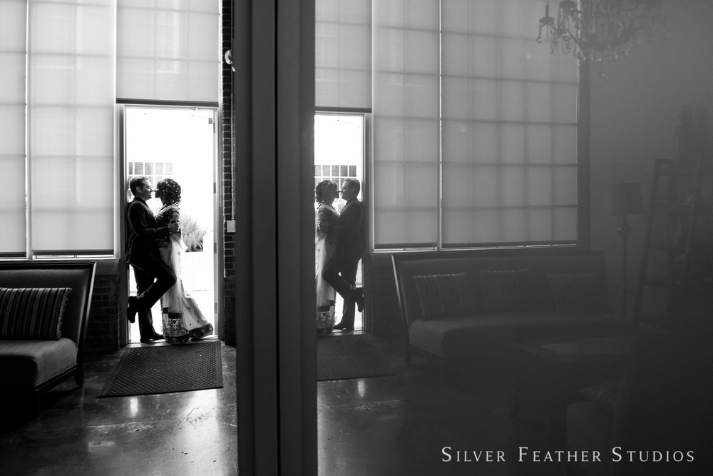 Reflection of the bride and groom in a doorway at their wedding at The Cotton Room. © Silver Feather Studios, wedding photography in Durham, NC.