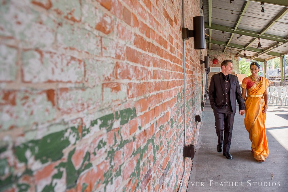 Rekha and Patrick walk along a brick wall together after their Cotton Room wedding ceremony in Durham. © Silver Feather Studios, Durham, NC wedding photographer