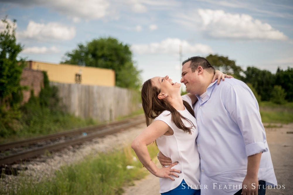 Brittany and Seth having a spontaneous moment of laughter at Raleigh warehouse district engagement session. © Silver Feather Studios
