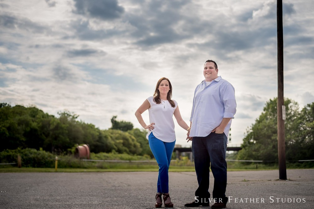Brittany and Seth stand against a lovely blue sky at their downtown Raleigh warehouse district engagement session. © Silver Feather Studios