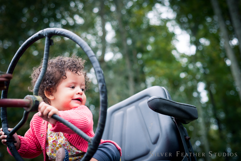 baby photographs on a tractor in rougemont nc, by silver feather studios, nc wedding photographer.