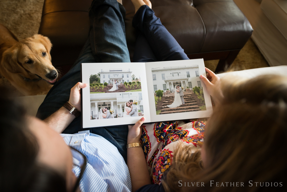 reviewing their wedding album together on their one year anniversary. © silver feather studios | wedding photographer in greensboro
