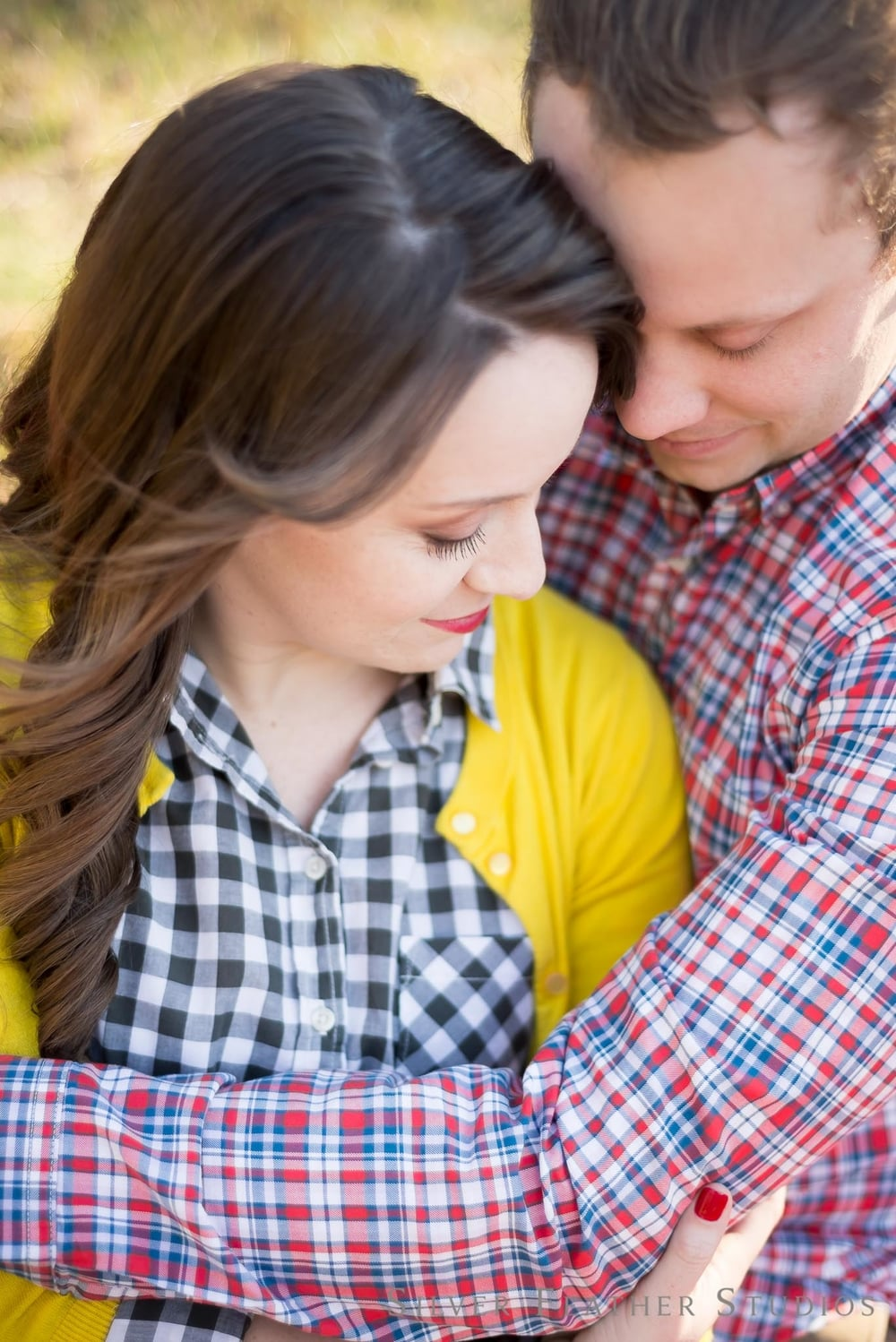 warm hugs and cuddling at Guilford courthouse national park. © engagement photography by silver feather studios