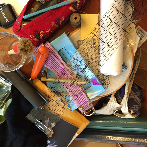 The current scene at my end of the dining room table. Up there: knitting, sewing, bookbinding, sewing machine repair, and a broken belt belonging to a kid.