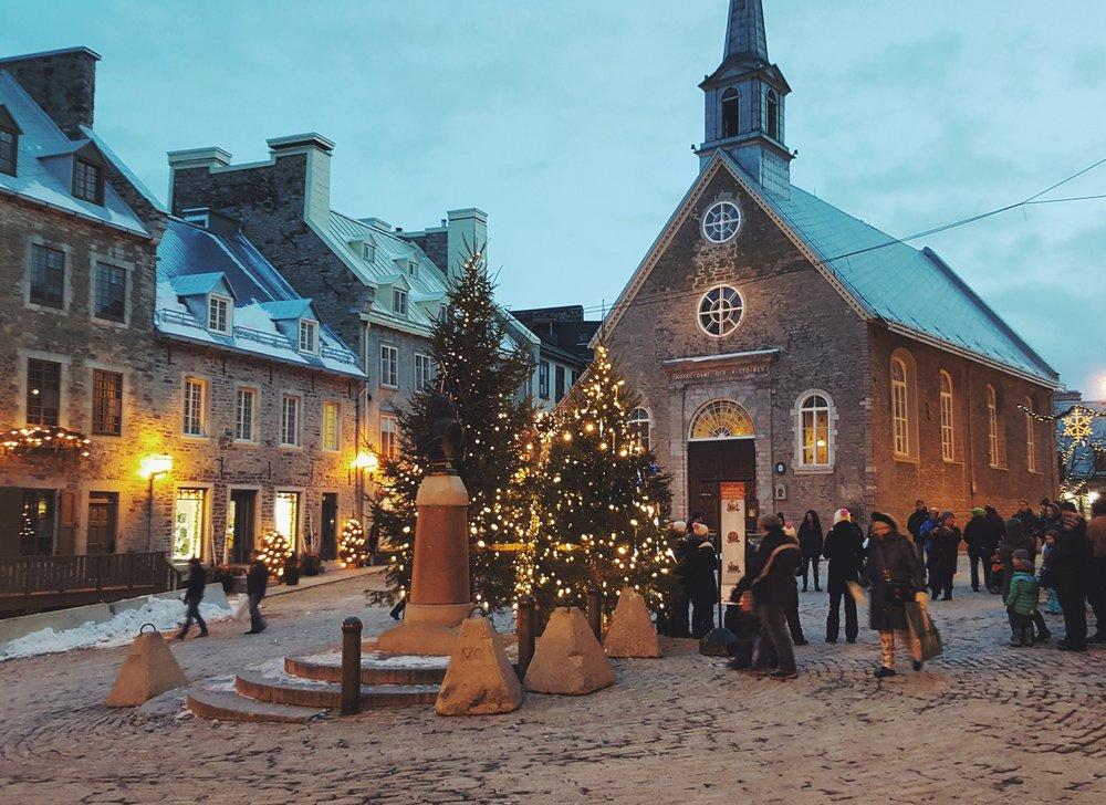 Carolers and shoppers in La Place Royale, a square in one of the oldest Quebec City neighborhoods.