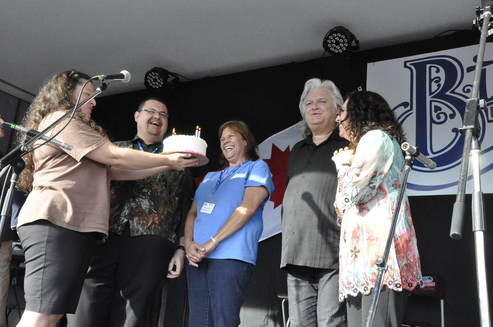 Volunteer Michelle Guidera presenting an Anniversary cake to Susan & Junior Sisk & Sharon White & Ricky Skaggs