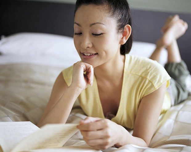 Professional woman on bed reading documents about her small business.