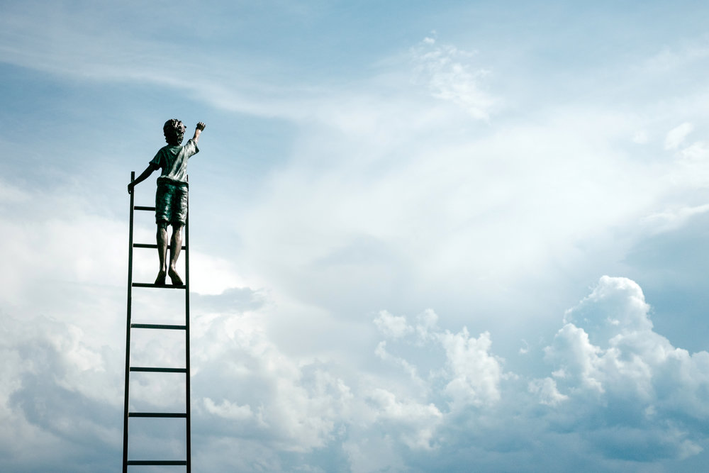 Boy on a ladder reaching for the blue sky reaching out in an attempt to touch it