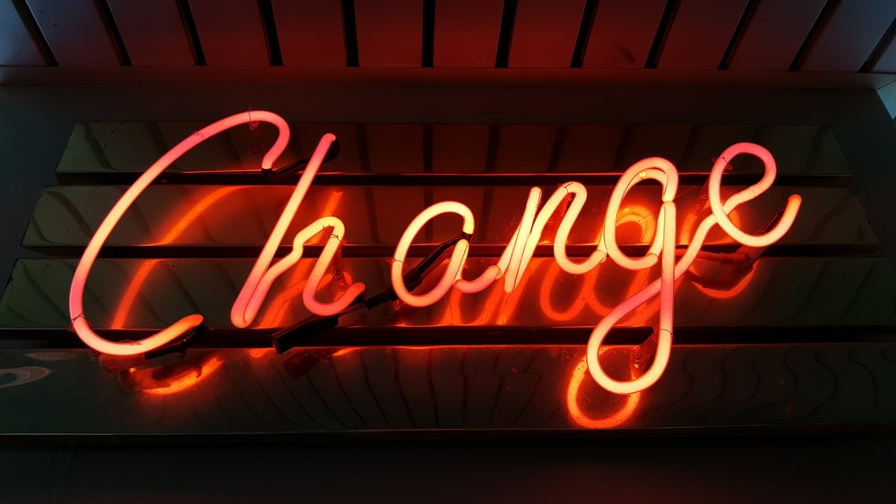The word change written in cursive neon