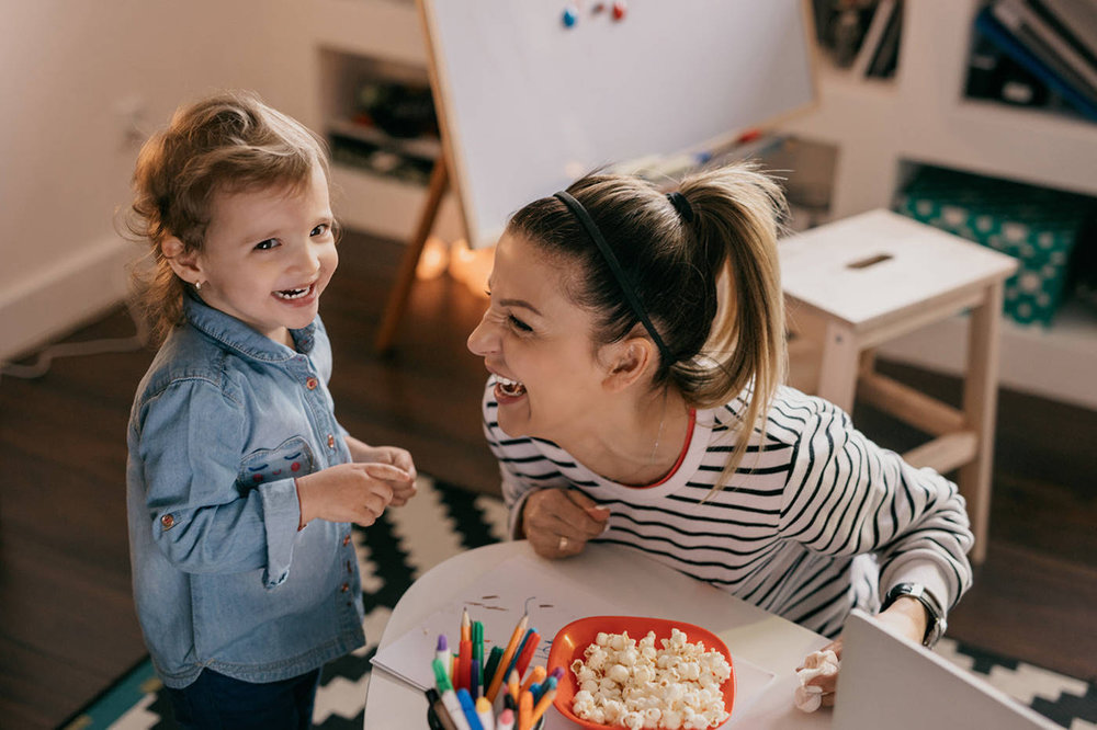 Woman and child laughing in the home.