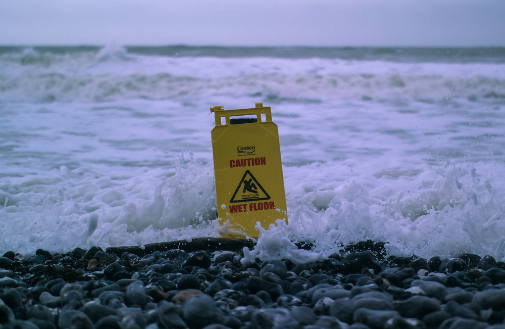 Caution wet floor a-frame sign in the surf.