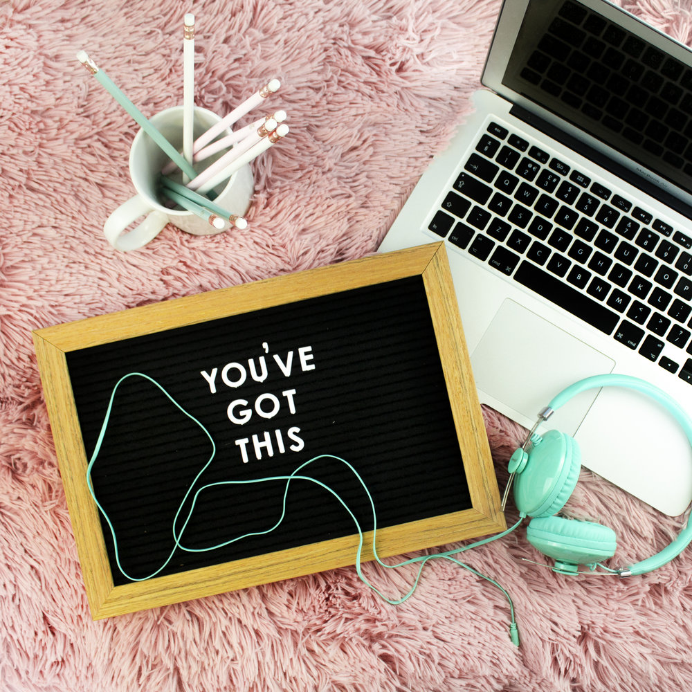 """Laptop, headphone and a sign reading """"You've got this"""" on carpet"""