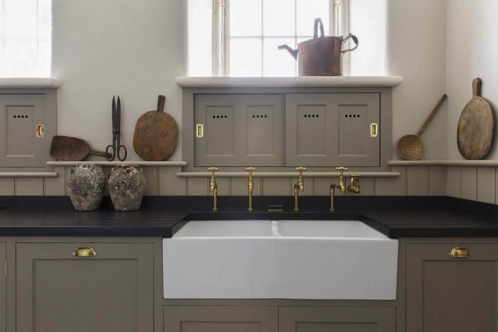 Antique accessories sit perfectly next to the ceramic sink and brass taps.