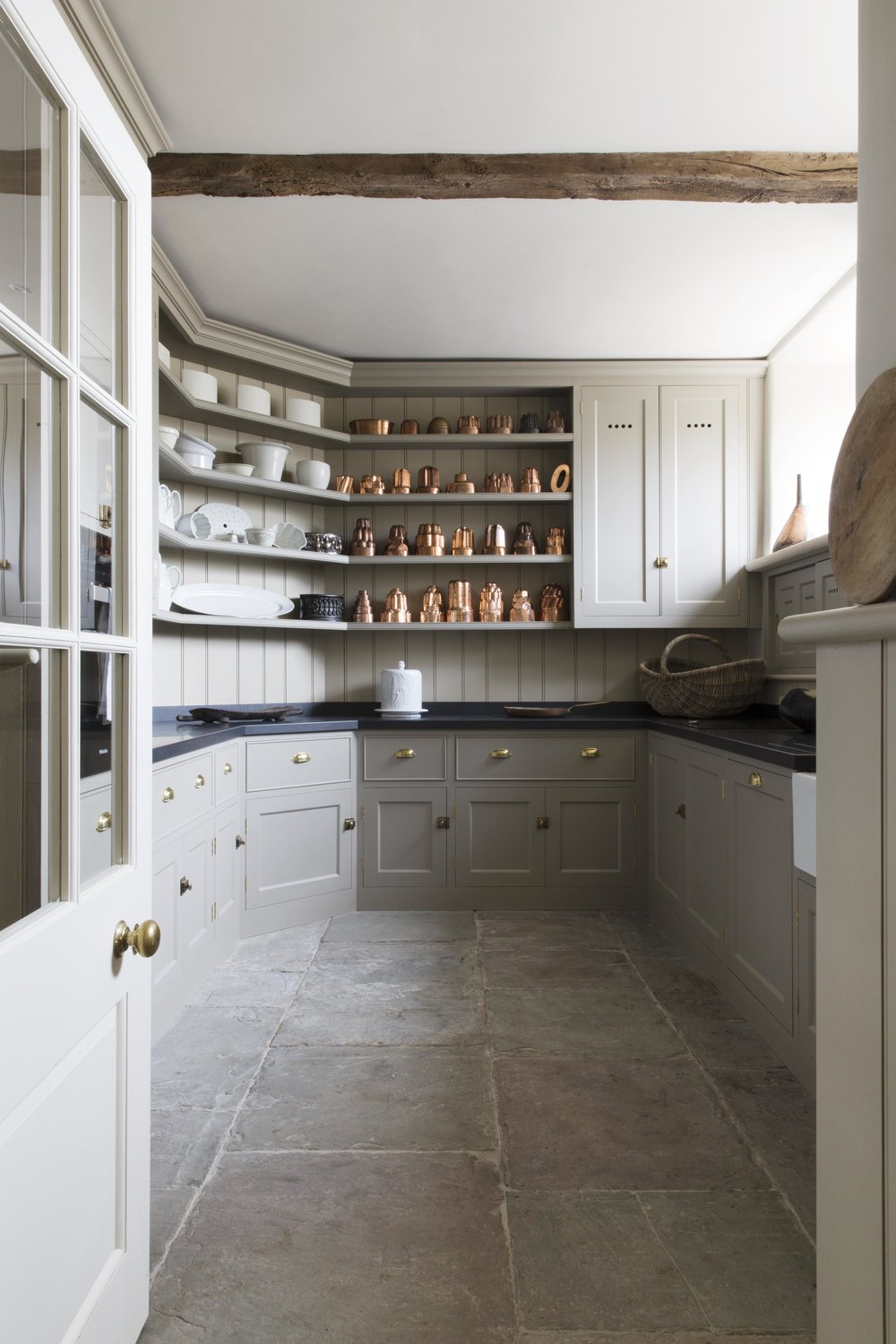 The muted colours of the cabinetry and york stone floor are great foils for the impressive collection of copper jelly moulds