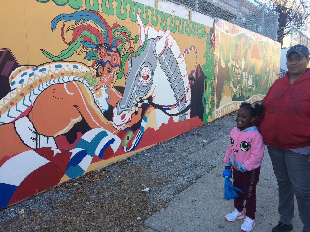 A mother and daughter out for a walk in their neighborhood stop by the mural
