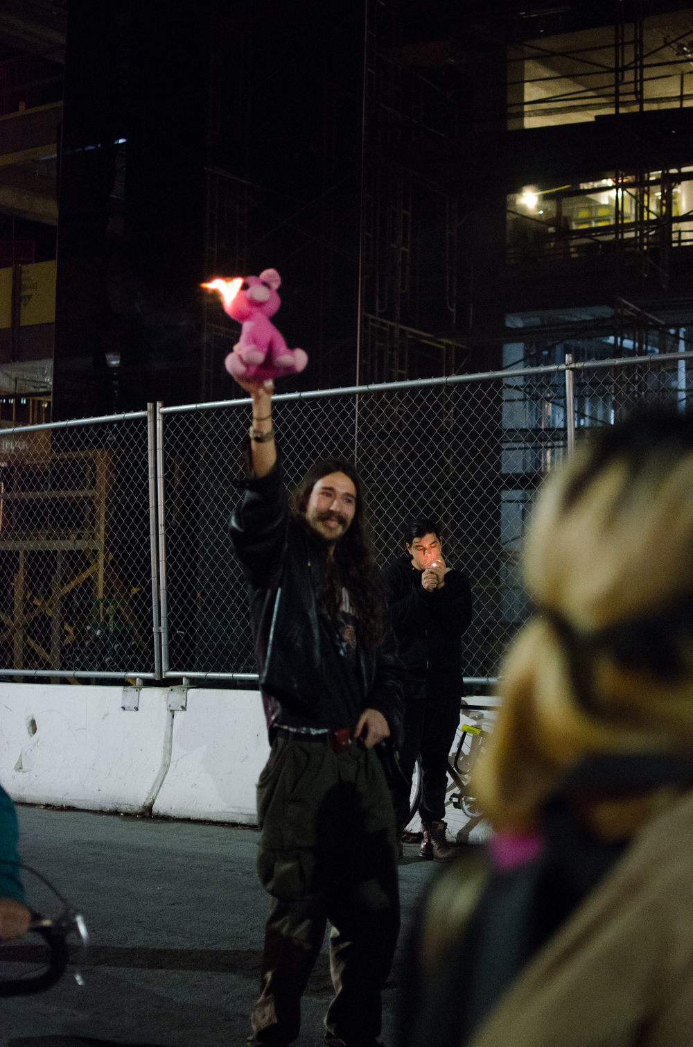 Man burns stuffed pig in front of ShareTea police line on Bancroft in Berkeley, CA December 6th, 2014 - photo by Kyle Cameron