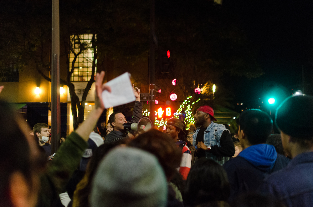 One of the men with a megaphone trying to speak to the crowd in front of the Berkeley Police Station on the night of December 8th, in Berkeley, CA - photo by Kyle Cameron