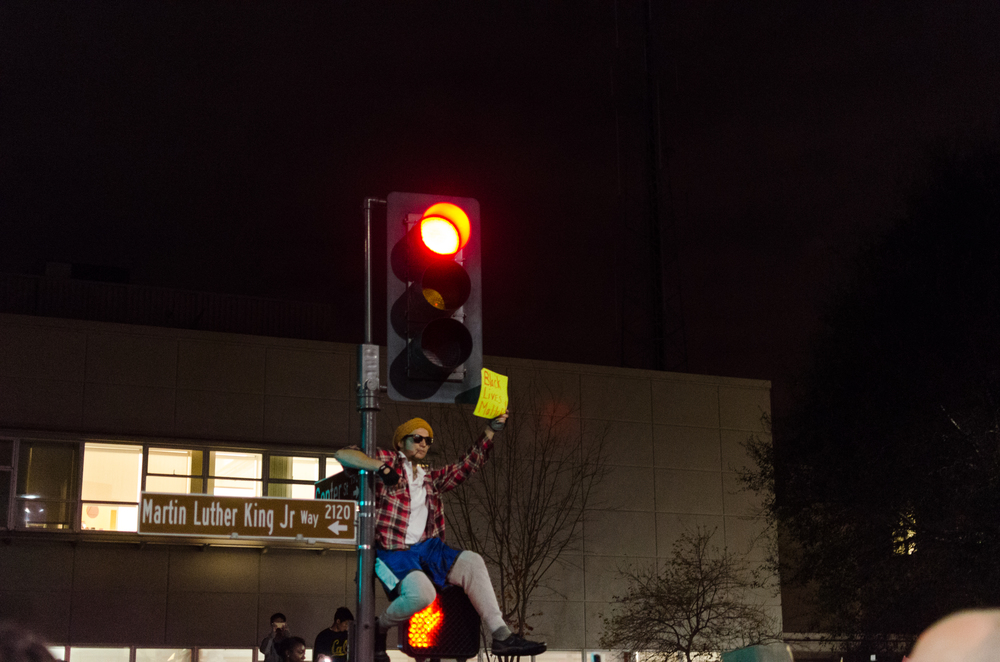 Man sits on signal post in front of Berkeley Police Station - photo by Kyle Cameron