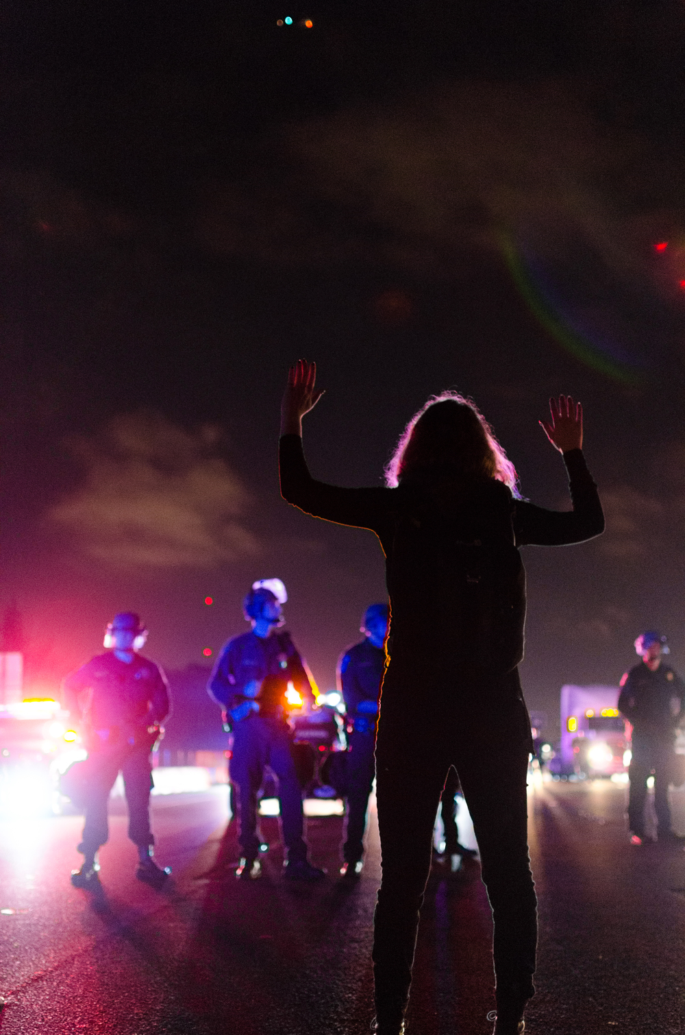 Woman facing police on the Northbound lane of Interstate 80 in Berkeley, CA on December 8th, 2014 - photo by Kyle Cameron