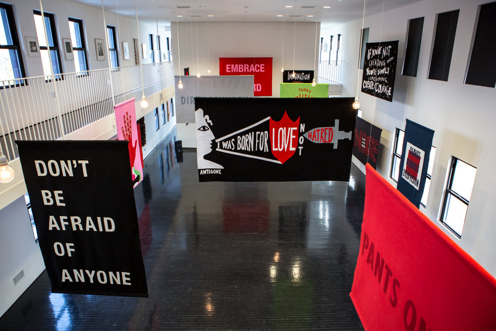 Word on the Street at The Watermill Center   ,  2017, felt political banner exhibition, House of Trees art collective (Amy + Jennifer Khoshbin).  Banners on view in this image:  Don't Be Afraid of Anyone : Laurie Anderson + A.M. Homes,  I was born for love not hatred : Amy Khoshbin + Anne Carson,  If you're not creating, you're simply consuming, create with courage : Wangechi Mutu,  Change Requires 2020 Vision : Carrie Mae Weems,  Pants on Fire : Jenny Holzer,  Open Palms Hold More : Naomi Shihab Nye + House of Trees,  Quiet Lives Inside Noise : Naomi Shihab Nye + HOT