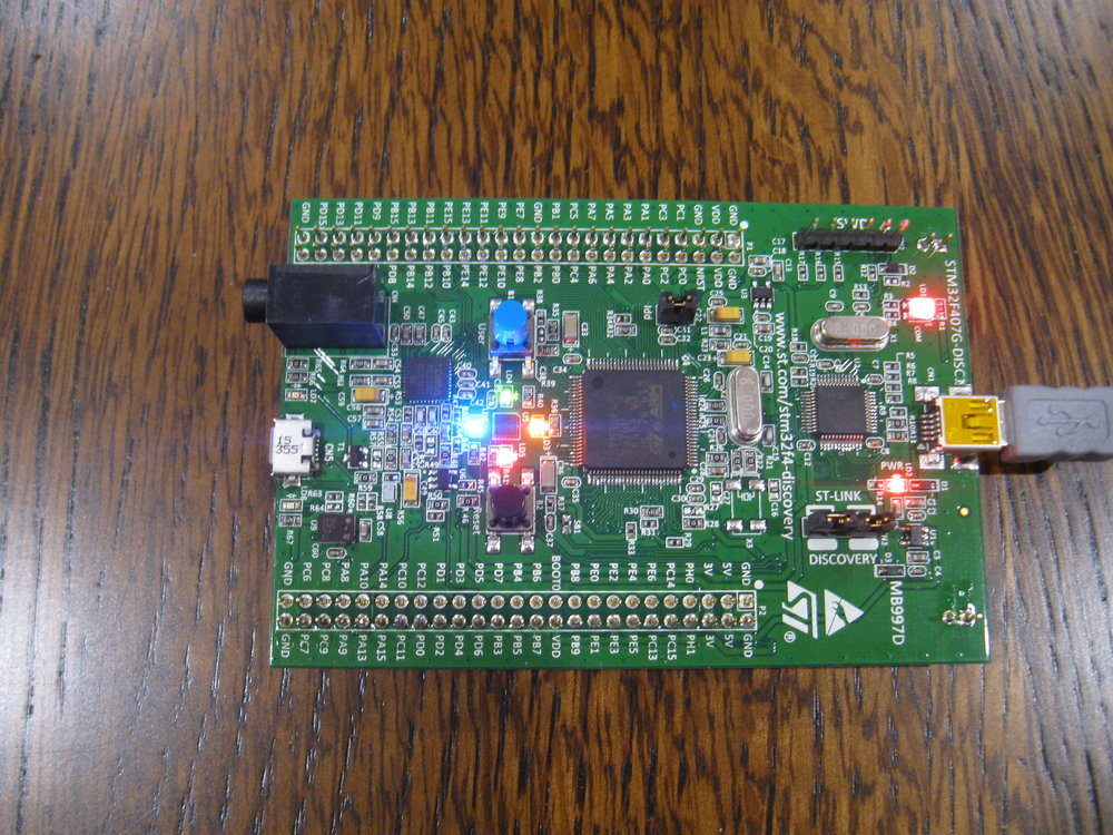 The DISC1 board running canned sample code, lighting the 4 LEDs that surround the accelerometer.