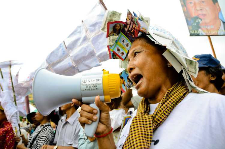 A woman shouts into a megaphone outside the Phnom Penh Municipal Court House. Supporters of jailed broadcaster Mam Sonando gathered to protest against his detention.