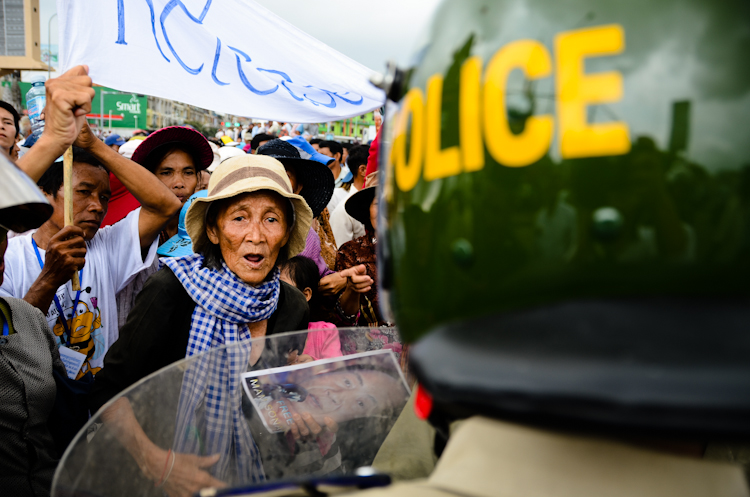 A woman faces police outside Phnom Penh Municipal Court House. Supporters of jailed broadcaster Mam Sonando gathered to protest against his detention.