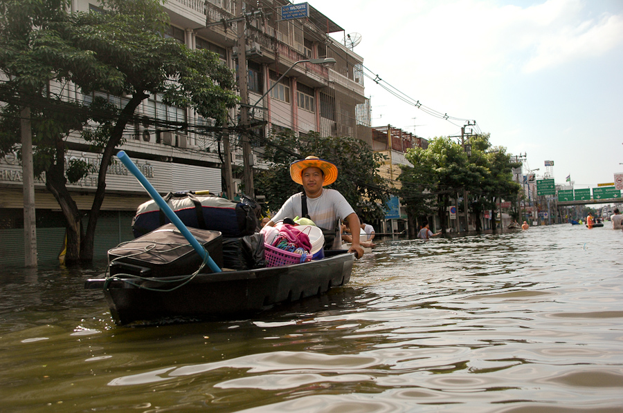A man floats his belongings to dry land, away from his home in a newly submerged Bangkok neighborhood.