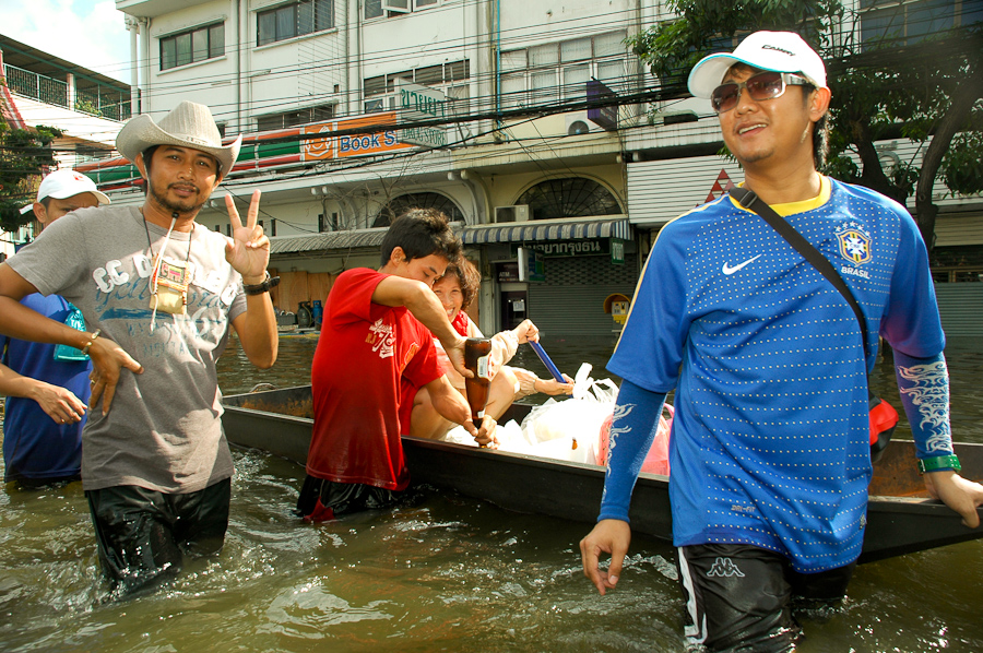 Bangkok residents float supplies in to their homes in a flooded neighborhood, while enjoying a drink.