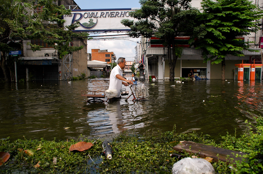 A man leaves a flooded Bangkok neighborhood.