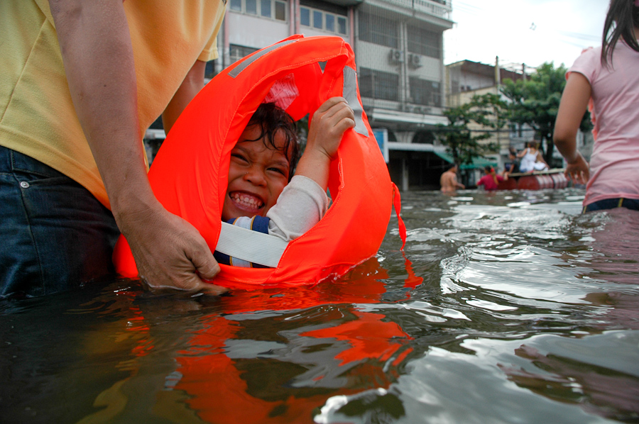 A toddler enjoys the water in a newly flooded Bangkok neighborhood.