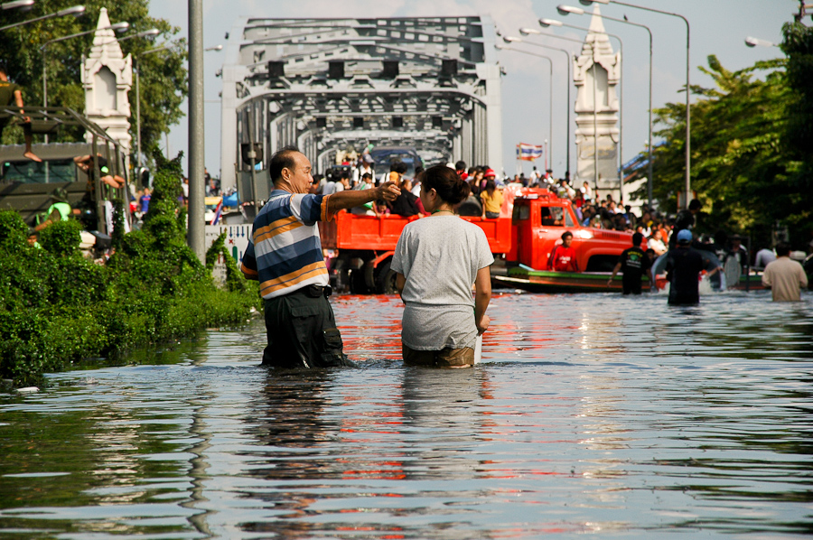 Residents leave a flooded Bangkok neighborhood.
