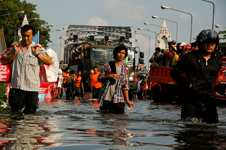 Residents bring supplies into a flooded neighborhood in western Bangkok.