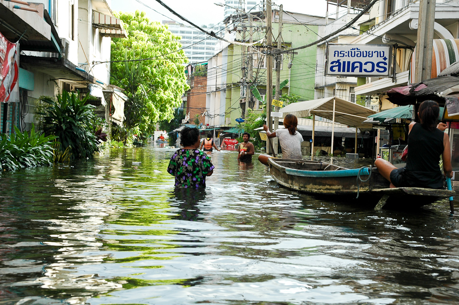 Residents walk and float through a flooded Bangkok neighborhood.